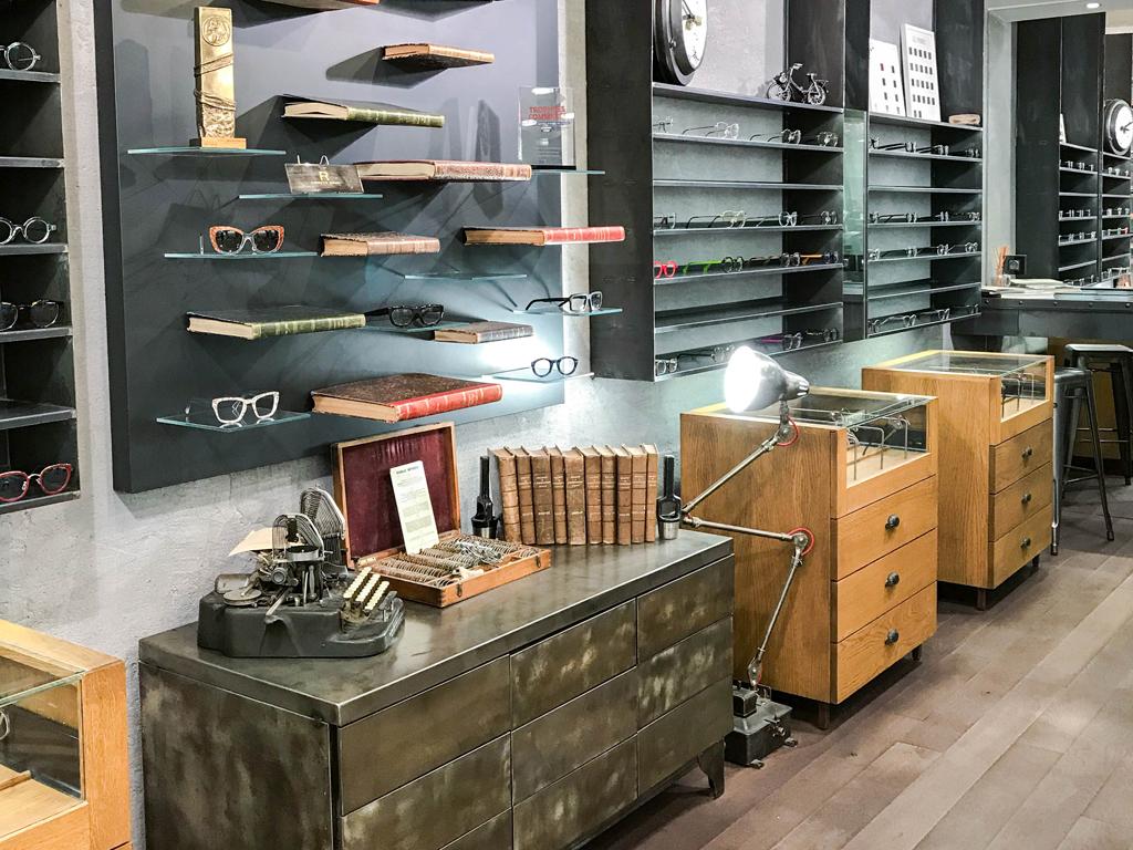 présentoirs du magasin regart meilleur opticien lunetier à Lyon étagères avec des livres et des lunettes