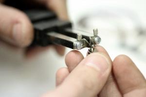 un opticien à Paris 1 ajuste une branche de lunette chez Les Lunettes du Pont Beuf