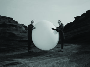 Femme et homme debout sur un rocher tenant un immense ballon blanc entre eux. Créateur de lunettes MATSUDA chez Eye-like