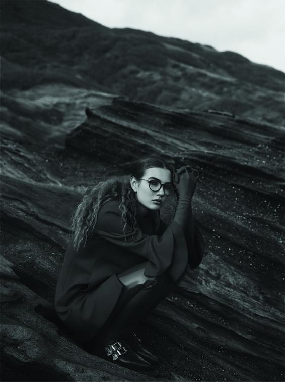 Jeune fille accroupie sur un rocher. Créateur de lunettes MATSUDA chez Eye-like