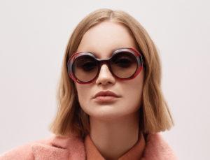 Femme assise avec un manteau et une chemise saumon, createur de lunettes Res Rei modele Cornet