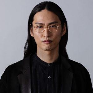 Jeune homme aux cheveux noir et longs partant des lunettes Kame Mannen