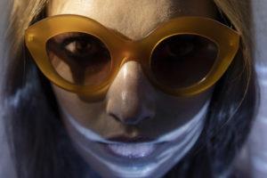 Visage proche d'une jeune femme sous l'eau avec des lunettes de soleil LAPIMA