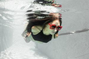 Jeune femme nageant sous la surface de l'eau avec des lunettes de soleil LAPIMA