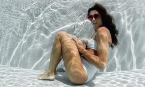 Jeune fille assise au fond de l'eau avec ses lunettes de marque LAPIMA