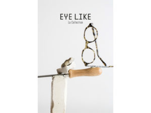 Présentation d'une monture de lunette écologique Eye Like, en équilibre sur un biseau à bois lui même en équilibre entre deux pierres